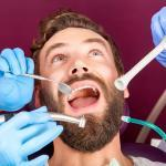 close up of men patient with beard with open mouth sitting in medical chair and doctor with assistant making teeth check up in dental clinic